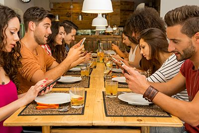 friends at restaurant using social media on smart phones